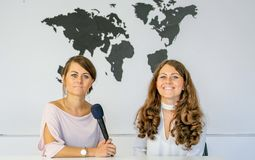 Journalists in studio. Two women in studio with microphone and world map on white background Royalty Free Stock Photography