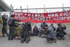 Protesters at the Kinder Morgan tank farm in Burnaby, BC on March 20th, 2018. Journalists surround protesters who have attached themselves to the front gate of royalty free stock image