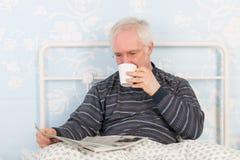Journaux de lecture d'homme supérieur dans le lit Image stock