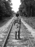 The journey. A young man and his guitar on the railroad tracks in b&w Stock Images