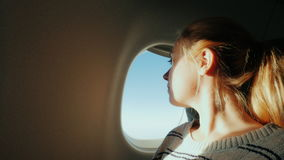 Journey in an airplane. Young woman opens a window, spotrit the window, enjoying the flight stock footage