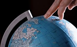 Journey around the world. Fingers walking on a globe, different lighting Stock Photos