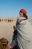 Journey on camel. This is a journey on camel in Sahara Desert. The woman dressed in bedouin's guise turned round and smile Royalty Free Stock Image