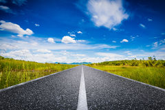 Journey concept with long road with green field. And blue sky Royalty Free Stock Photo