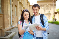 On journey. Couple of travelers studying map of ancient town during their journey Royalty Free Stock Image