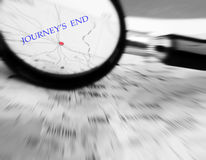 Journey end concept. A conceptual image of a magnifying glass focused on a destination red dot on a map, marked with the words journey's end.  Travel concept Royalty Free Stock Photo