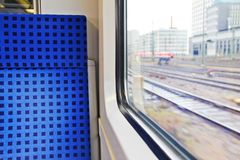 Journey by fast train. Comfortable seat nearby german train big window with city view Royalty Free Stock Photos