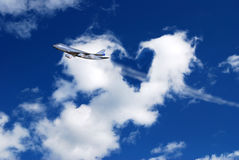 Journey gift. White clouds creating the shape of a heart on a deep blue sky as a plane crosses  them Royalty Free Stock Photo