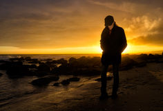 Journey. Lonely Walker. Young woman walking along the seashore at sunset Stock Photo