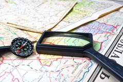 Journey preparation. Compass and lens laying on the maps Stock Image