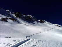 Journey's path. Ski track up into the mountain from left bottom of frame to right top with navy blue sky Stock Photography