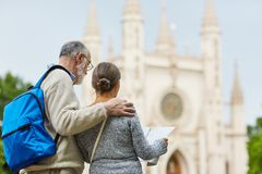 Journey of seniors. Aged tourists with guide standing in front of historical building during their journey stock photography