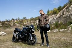 Journey to a motorcycle through a career. A motorcyclist with a helmet in his hands looks at a motorcycle stock photo