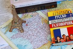 Journey to Paris, learning french. Decorative Eiffel Tower on a map of France, textbooks and books stock images