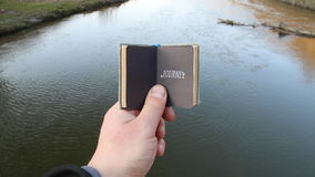 Journey, traveler, trip, vacation, visit, idea. Traveler holds a book with text On the background of a beautiful river. The traveler holds a book with the stock footage