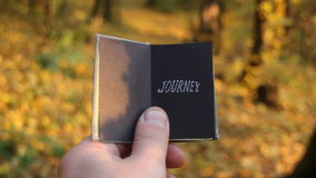 Journey Trip Travel Discover Explore idea. Hand holding a book with the inscription Journey stock video