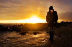 Journey. Walking Along the Seashore. Young Woman walking along the seashore at sunset Royalty Free Stock Photos