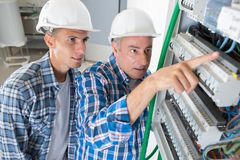 Journeyman and apprentice electrician working to repair circuit panel Stock Photos