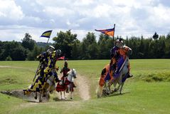 Jousting knights, warriors, fighters riding horses Stock Images