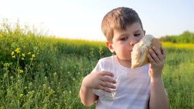 Jovem bonito com pão e vidro do naco à disposição no campo do fundo, rapaz pequeno que come o alimento no parque fora filme