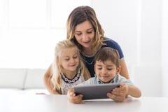 Jovem criança adorável do irmão e da irmã que usa a tabuleta com mãe imagens de stock