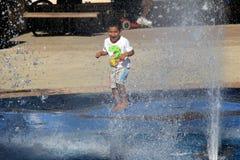 Jovem criança no jogo na fonte de água, praia de Hollywood, Miami, 2014 Imagens de Stock