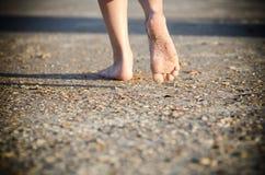 Jovem criança que anda com os pés descalços em uma praia Imagem de Stock