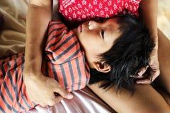 Jovem criança que dorme no regaço da mãe imagens de stock
