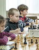 Jovem criança que faz um movimento com um cavalo durante um competiam da xadrez em uma escola, com diversos outros concorrentes n Foto de Stock