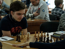 Jovem criança que faz um movimento com um cavalo durante um competiam da xadrez em uma escola, com diversos outros concorrentes n Fotos de Stock Royalty Free