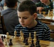 Jovem criança que faz um movimento com um cavalo durante um competiam da xadrez em uma escola, com diversos outros concorrentes n Imagem de Stock