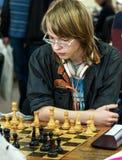 Jovem criança que faz um movimento com um cavalo durante um competiam da xadrez em uma escola, com diversos outros concorrentes n Fotos de Stock