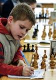 Jovem criança que faz um movimento com um cavalo durante um competiam da xadrez em uma escola, com diversos outros concorrentes n Imagem de Stock Royalty Free