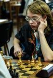 Jovem criança que faz um movimento com um cavalo durante um competiam da xadrez em uma escola, com diversos outros concorrentes n Imagens de Stock Royalty Free