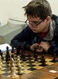 Jovem criança que faz um movimento com um cavalo durante um competiam da xadrez em uma escola, com diversos outros concorrentes n Fotografia de Stock