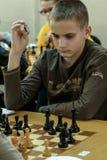 Jovem criança que faz um movimento com um cavalo durante um competiam da xadrez em uma escola, com diversos outros concorrentes n Imagens de Stock