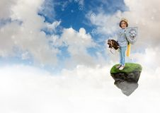 A jovem criança vestida como um cavaleiro que joga na plataforma de flutuação da rocha no céu com conectores conecta fotografia de stock