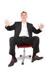 Jovem de riso na cadeira do escritório imagem de stock royalty free
