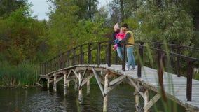 Jovem Família na Ponte Wooden por um Lago filme
