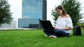 Jovem morena sentada na grama e usa laptop, digitando no teclado, construindo um vidro de negócios moderno sobre o fundo filme
