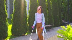 Jovem mulher à moda bonita positiva com um ferimento que anda em muletas através do parque na cidade de ensolarado vídeos de arquivo