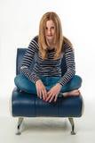 Jovem mulher à moda bonita que senta-se de pernas cruzadas imagem de stock royalty free