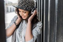 A jovem mulher à moda bonito alegre está apreciando a música fotos de stock