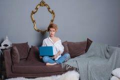 Jovem mulher à moda com o portátil nas mãos no sofá e vista da câmera Vestido em uma camisa branca e em calças de brim com bordad Imagem de Stock Royalty Free