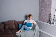 Jovem mulher à moda com o portátil nas mãos no sofá e vista da câmera Vestido em uma camisa branca e em calças de brim com bordad Imagens de Stock Royalty Free