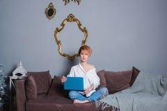 Jovem mulher à moda com o portátil nas mãos no sofá e vista da câmera Vestido em uma camisa branca e em calças de brim com bordad Fotos de Stock