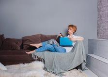 Jovem mulher à moda com o portátil nas mãos no sofá e vista da câmera Vestido em uma camisa branca e em calças de brim com bordad Fotografia de Stock