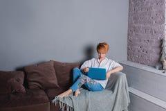 Jovem mulher à moda com o portátil nas mãos no sofá e vista do portátil Vestido em uma camisa branca e em calças de brim com bord Imagens de Stock Royalty Free