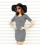 Jovem mulher à moda em vestido listrado, chapéu de palha do verão que levanta na parede branca fotografia de stock