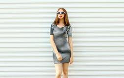 Jovem mulher à moda em vestido listrado que levanta na parede branca imagens de stock